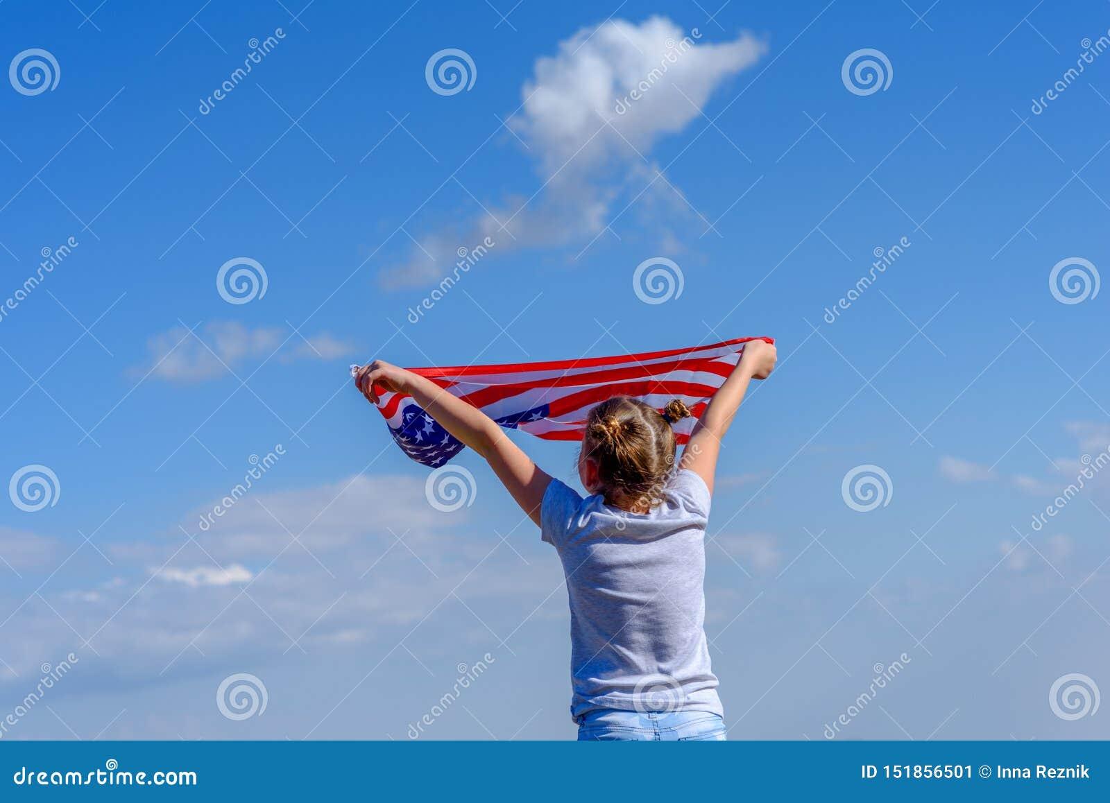 E Счастливый ребенк, милая девушка маленького ребенка с американским флагом США празднуют 4-ое -го июль