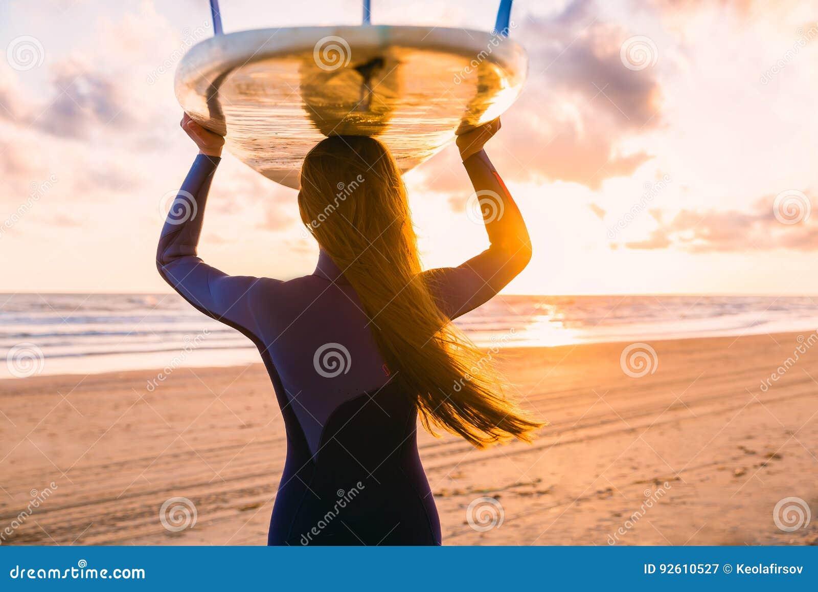 E 有冲浪板的妇女在日落或日出的一个海滩 冲浪者和海洋