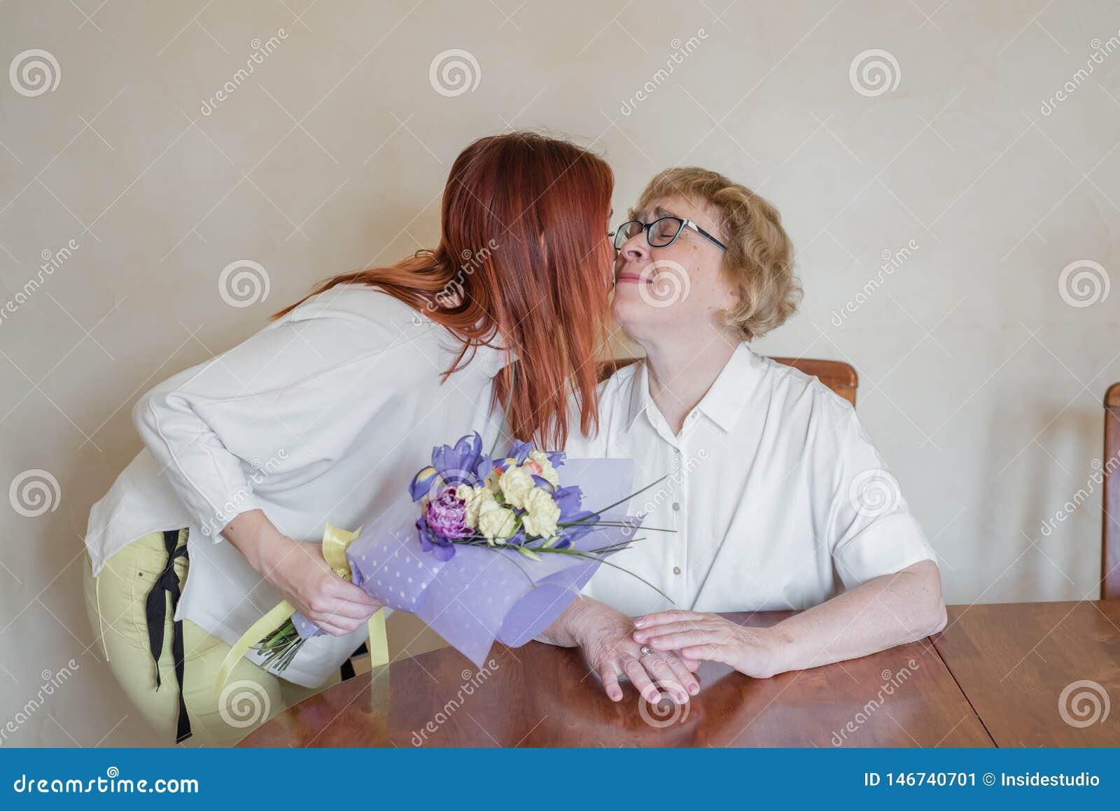 E 给花照顾和亲吻她的女儿在面颊 花费时间一起,