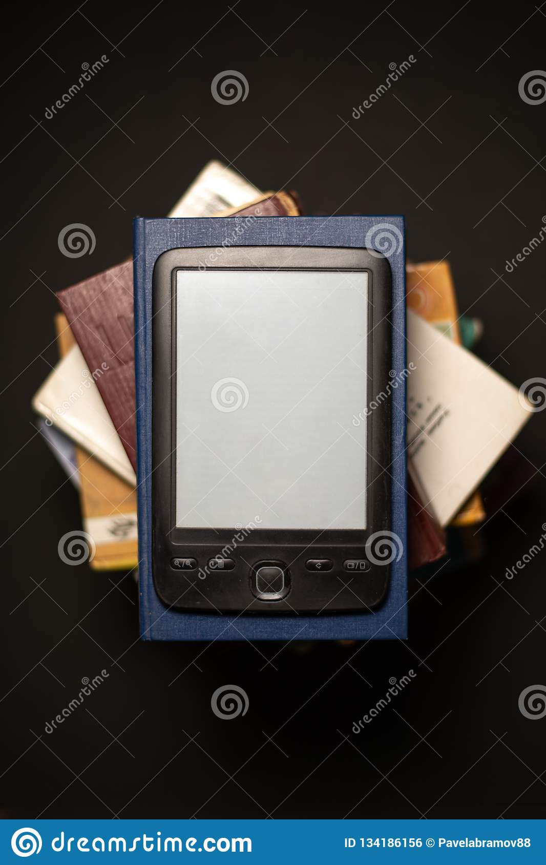E-book on a stack of ordinary paper books