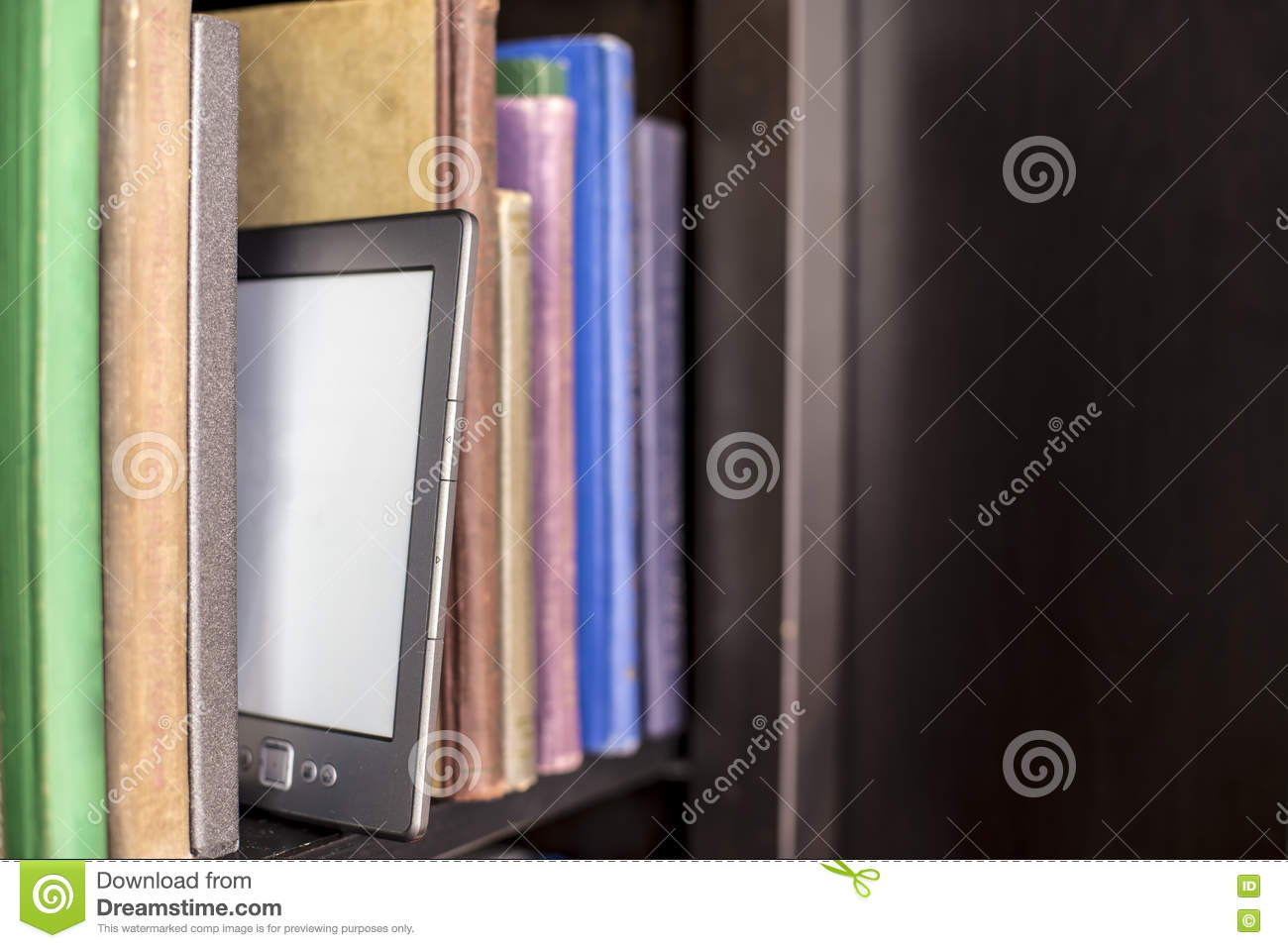 E Book Stands On A Wooden Bookshelf Filled With Old Paper Books
