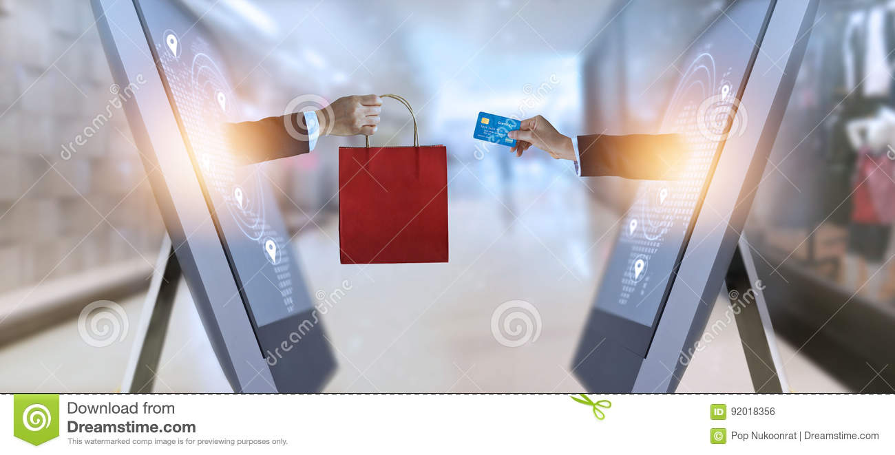 E-commerce, hand holding shopping bag and credit card from screen and global network, shopping and payments online concept