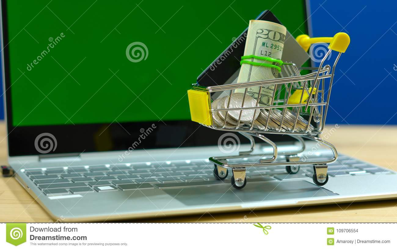 E-commerce shopping concept with miniature shopping cart and modern laptop.