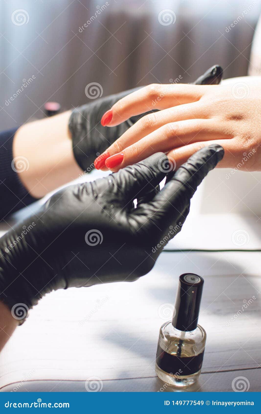 E De manicure schildert spijkers met rood nagellak De salon van de manicureschoonheid