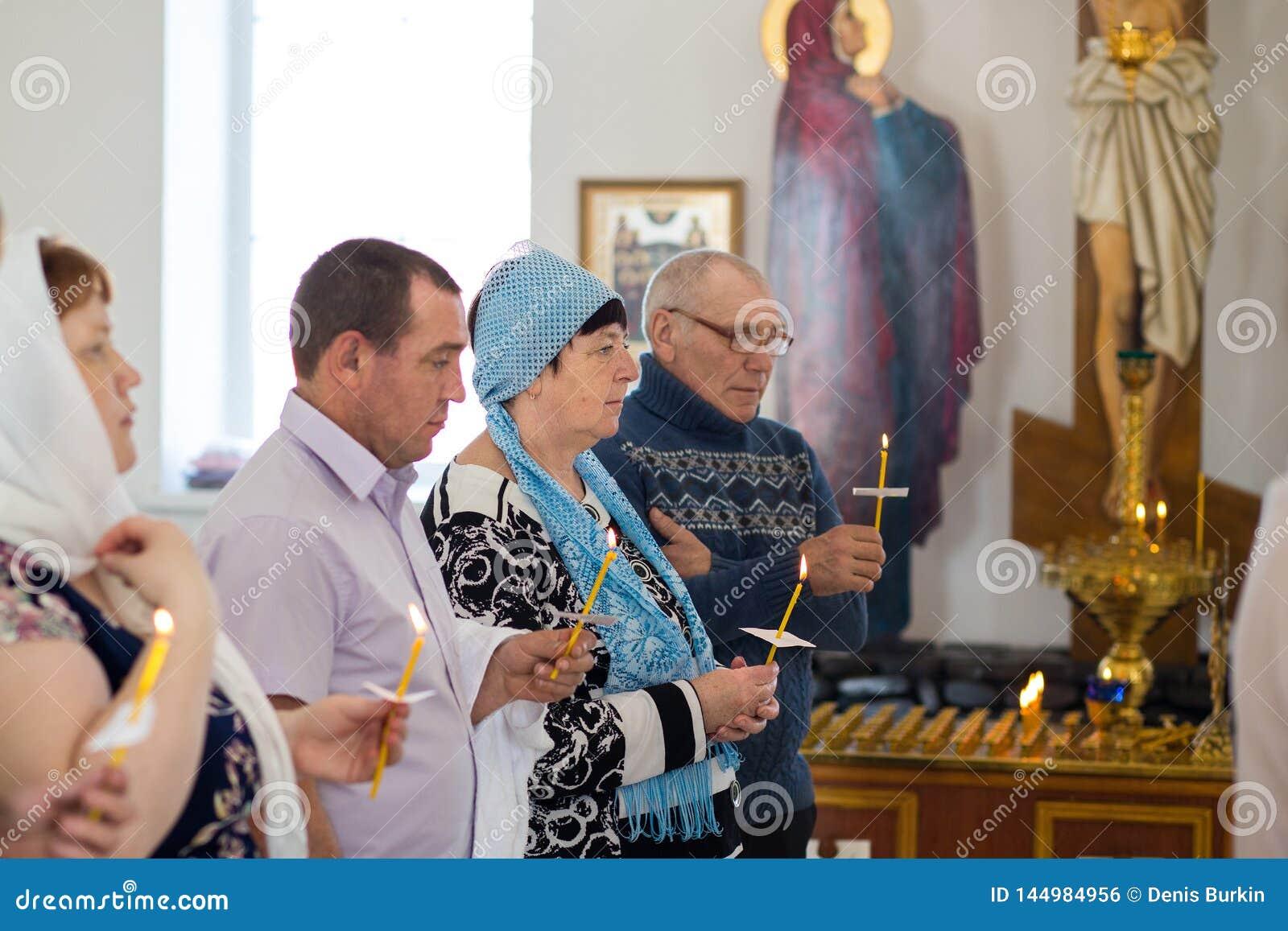 E de mensen houden kaarsen tijdens het ritueel van doopsel in de Orthodoxe Kerk