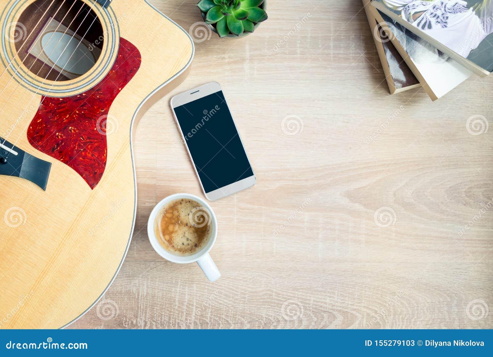 E Gitarr, böcker, kopp kaffe, telefon och suckulenta växter över träbakgrund r