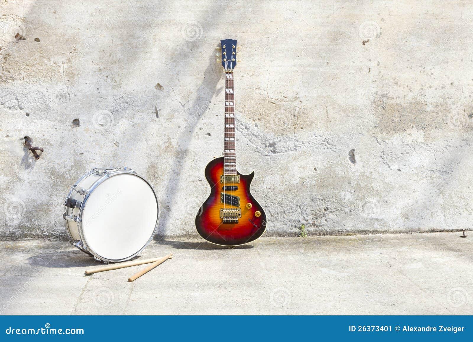 E-Gitarre und Trommel vor einer Weinlesewand