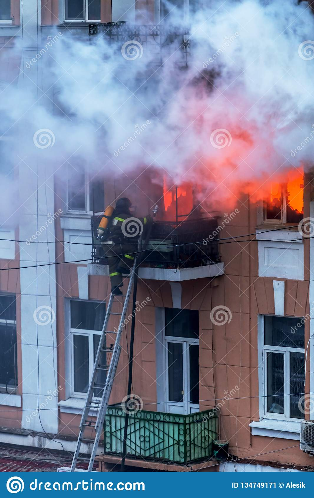 E Het sterke heldere licht en de clubs, rook betrekken venster van hun brandend huis brandbestrijders