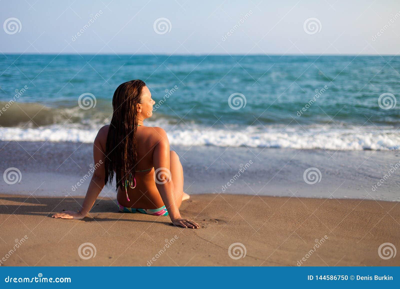 E Junge Frau, die vor der Küste sitzt r Frau