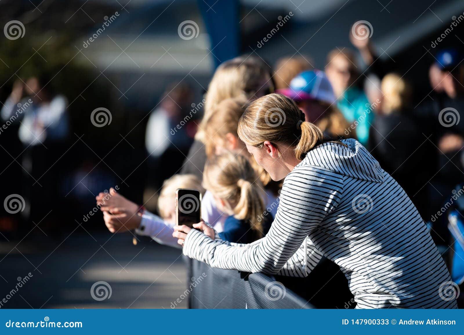 E Kvinnavideolöpare på hennes telefon omkring som ska avslutas på hem- elasticitet