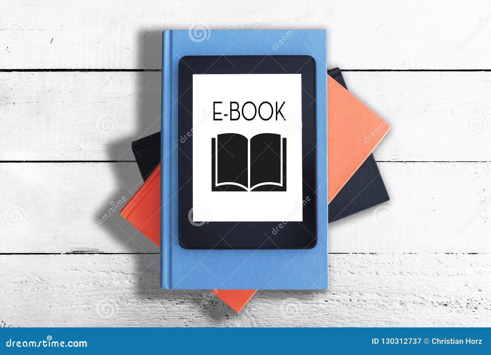 E-leitor na pilha de livros contra a tabela de madeira rústica branca