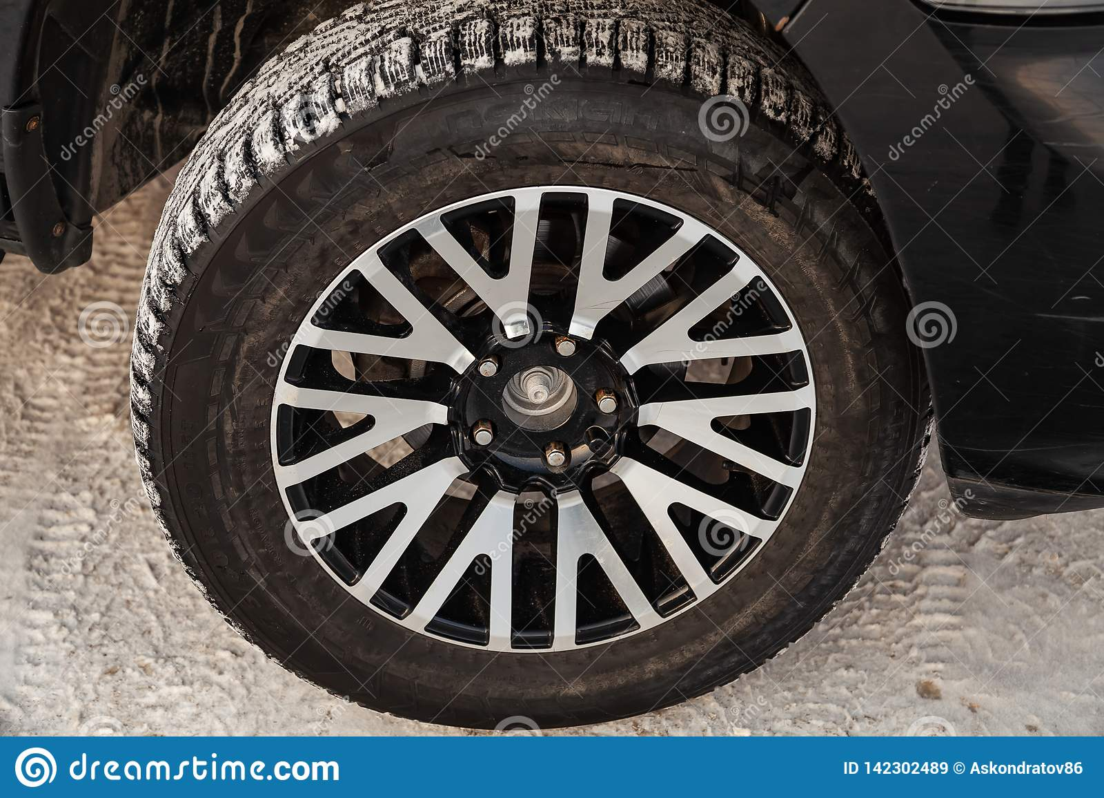 E 7 litrów frontowego koła widoku na samochodowym parking z śnieżnym tłem