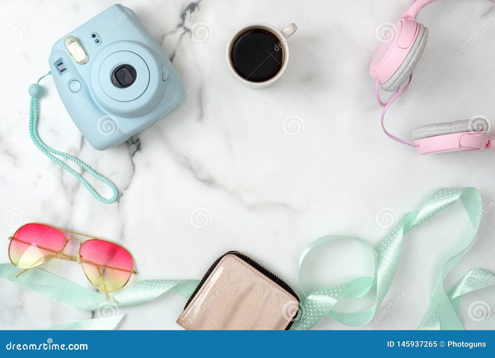 E Modern fotokamera, kopp kaffe, handv?ska, solglas?gon, h?rlurar p? marmor