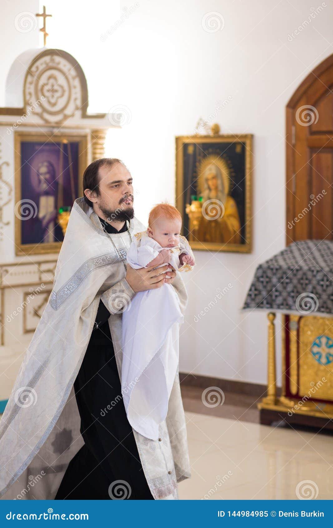 E Orthodoxe priester die een baby houden tijdens het doopselritueel