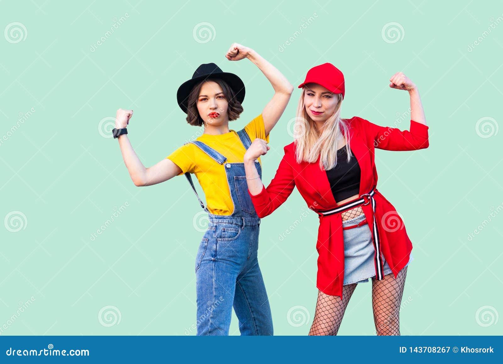 E Portret van twee mooie modieuze hipstermeisjes die en zich daar macht bevinden tonen,
