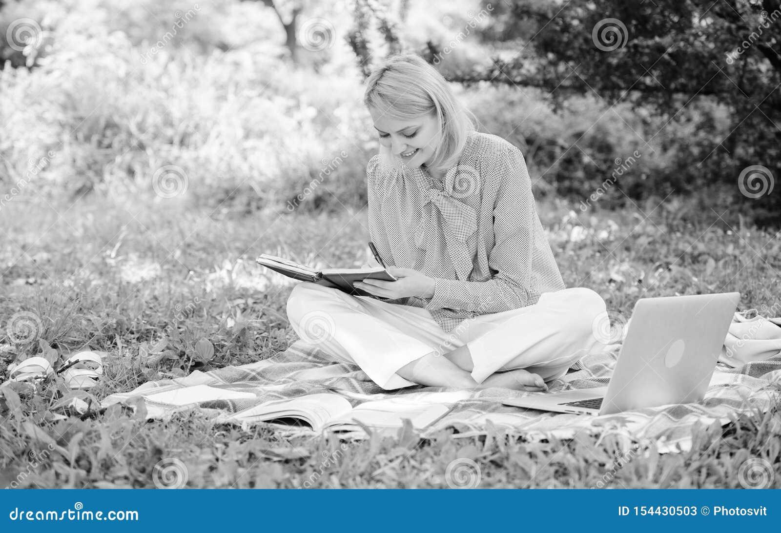 拿着笔记本的女人坐在地毯草地上 带记事本写便笺的女孩 自由职业概念 指南开始