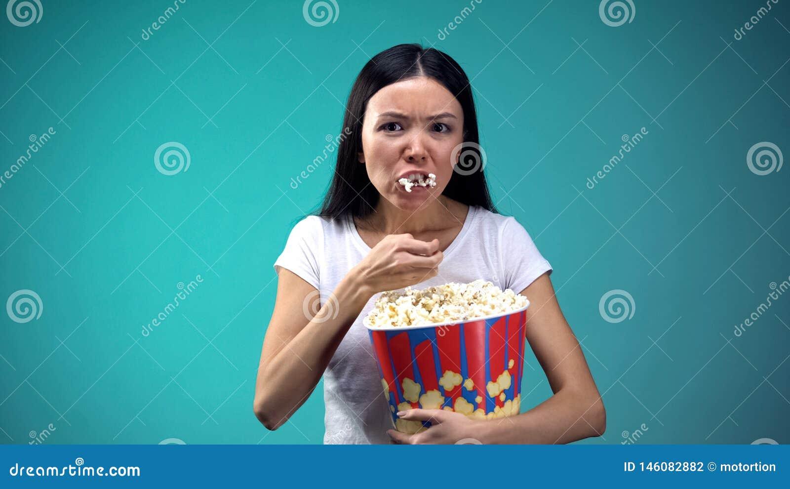 集中于从大纸杯的电影妇女吞食的玉米花,不健康吃