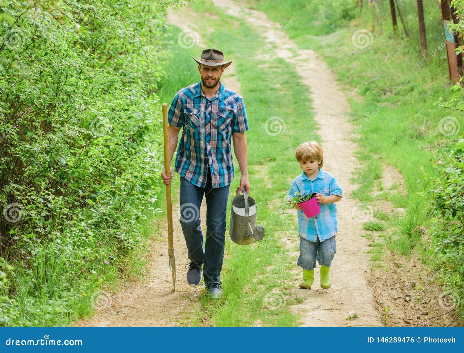 Jongen en vader in de natuur met drenken en schoppen Vader onderwijst zorginstellingen Arbor-dag Aanplantbomen Boom