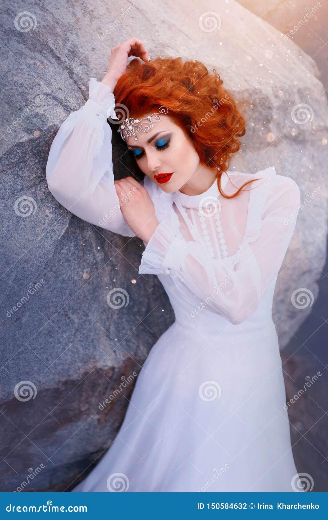 Princesa del pelirrojo en un vestido blanco del vintage que miente en las piedras Equipo lujoso con las mangas de aire Belleza du
