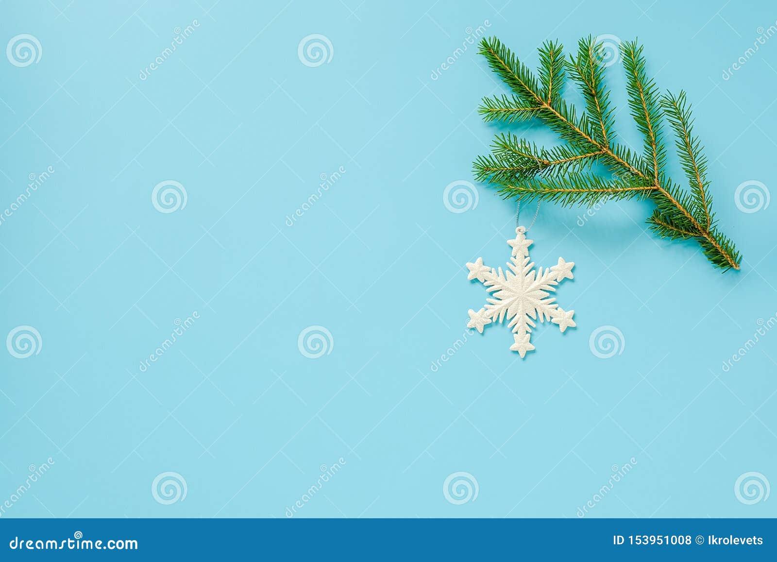 Brancos, decoração de Natal, brinquedo em floco de neve, sobre ramo de éter azul Conceito Feliz Natal ou Feliz Ano Novo Copiar es