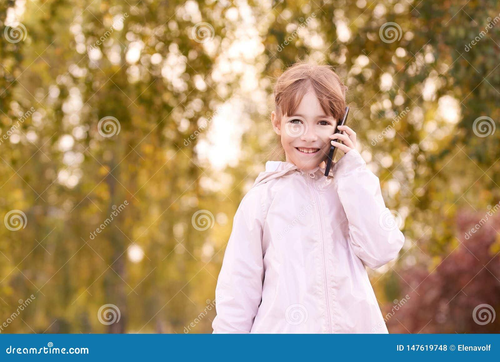 Joven feliz habla de celular roaming telefónico Personas con smartphone Fondo del otoño