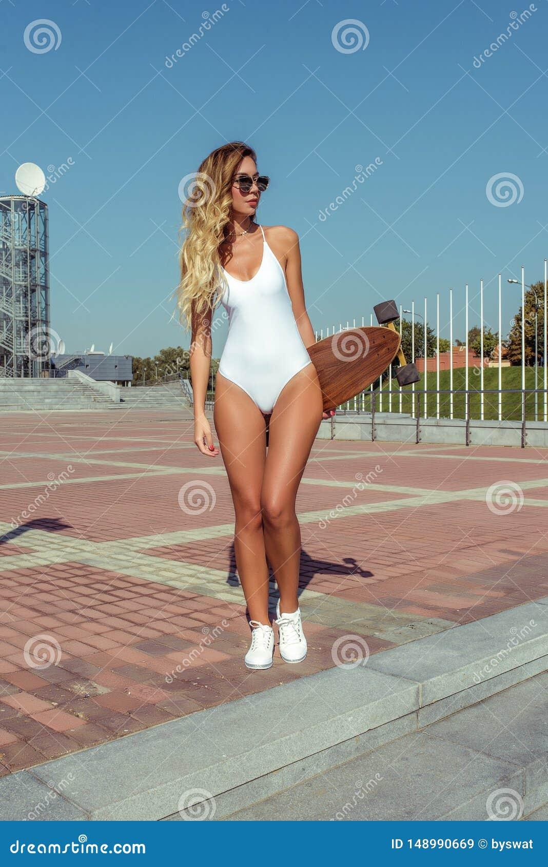Όμορφη γυναίκα με μακριά μαλλιά, με παραγάδι, κορίτσι καλοκαίρι στην πόλη Αθλητικά παπούτσια με λευκά μαγιό Έννοια
