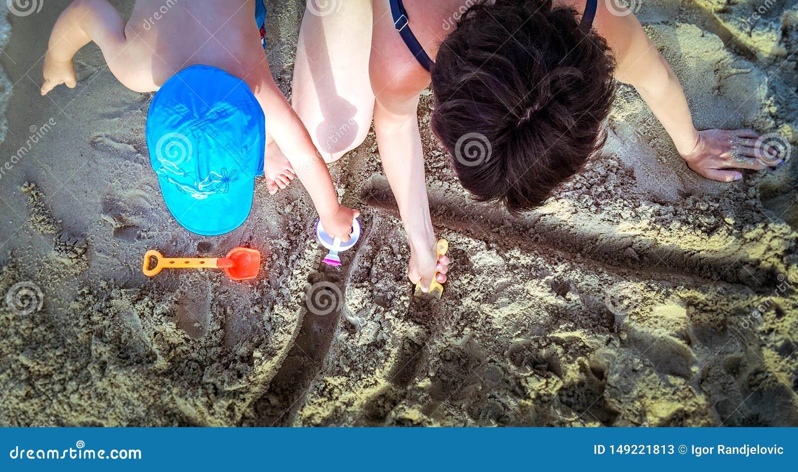 Μητέρα και ένα παιδί που έχει τη διασκέδαση στην παραλία r