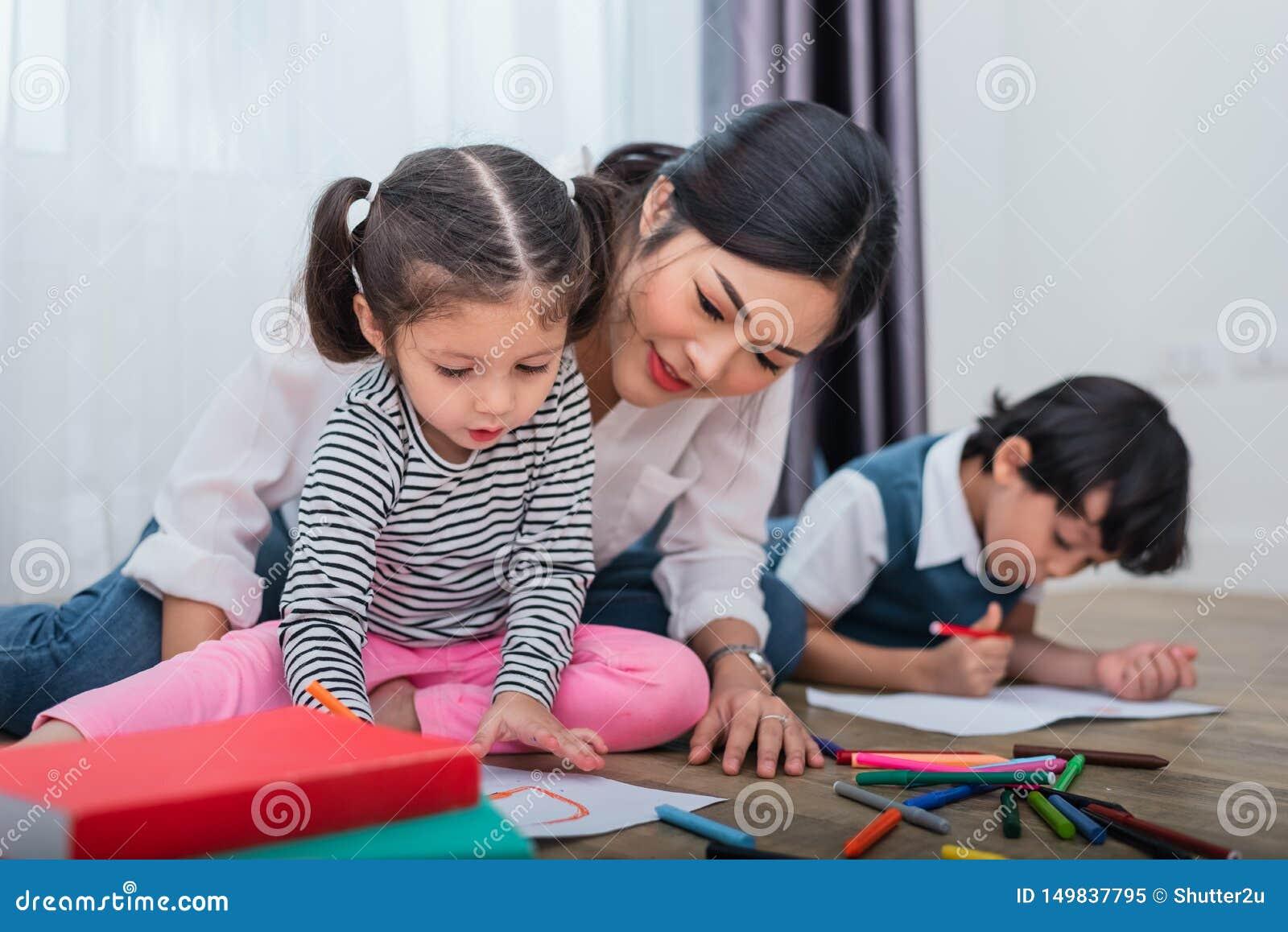 母亲图画班的教学孩子 与五颜六色的蜡笔颜色的女儿和儿子绘画在家 师范训练学生