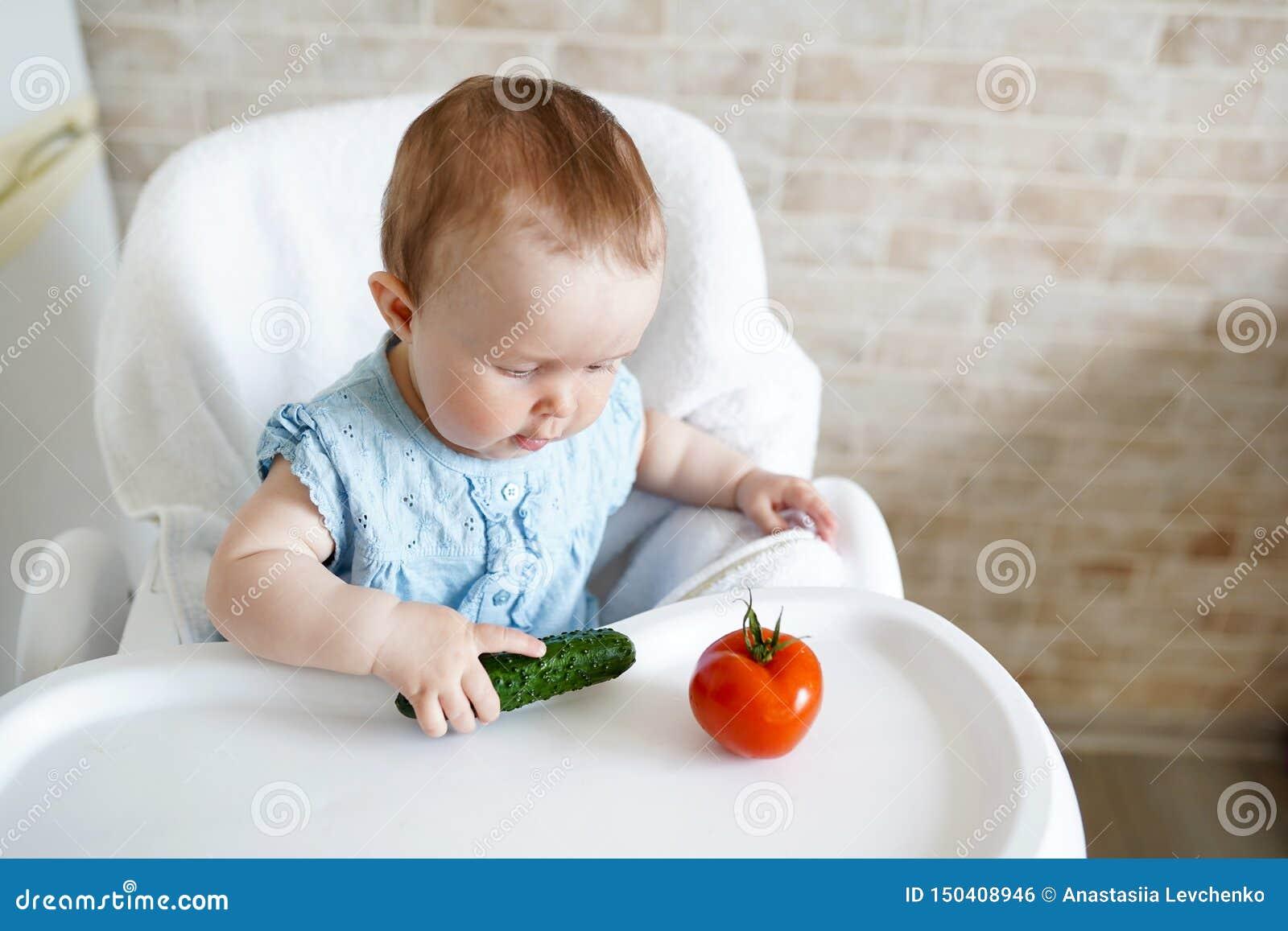 Младенец есть овощи зеленый огурец в руке маленькой девочки в солнечной кухне Здоровое питание для детей Закуска или завтрак для