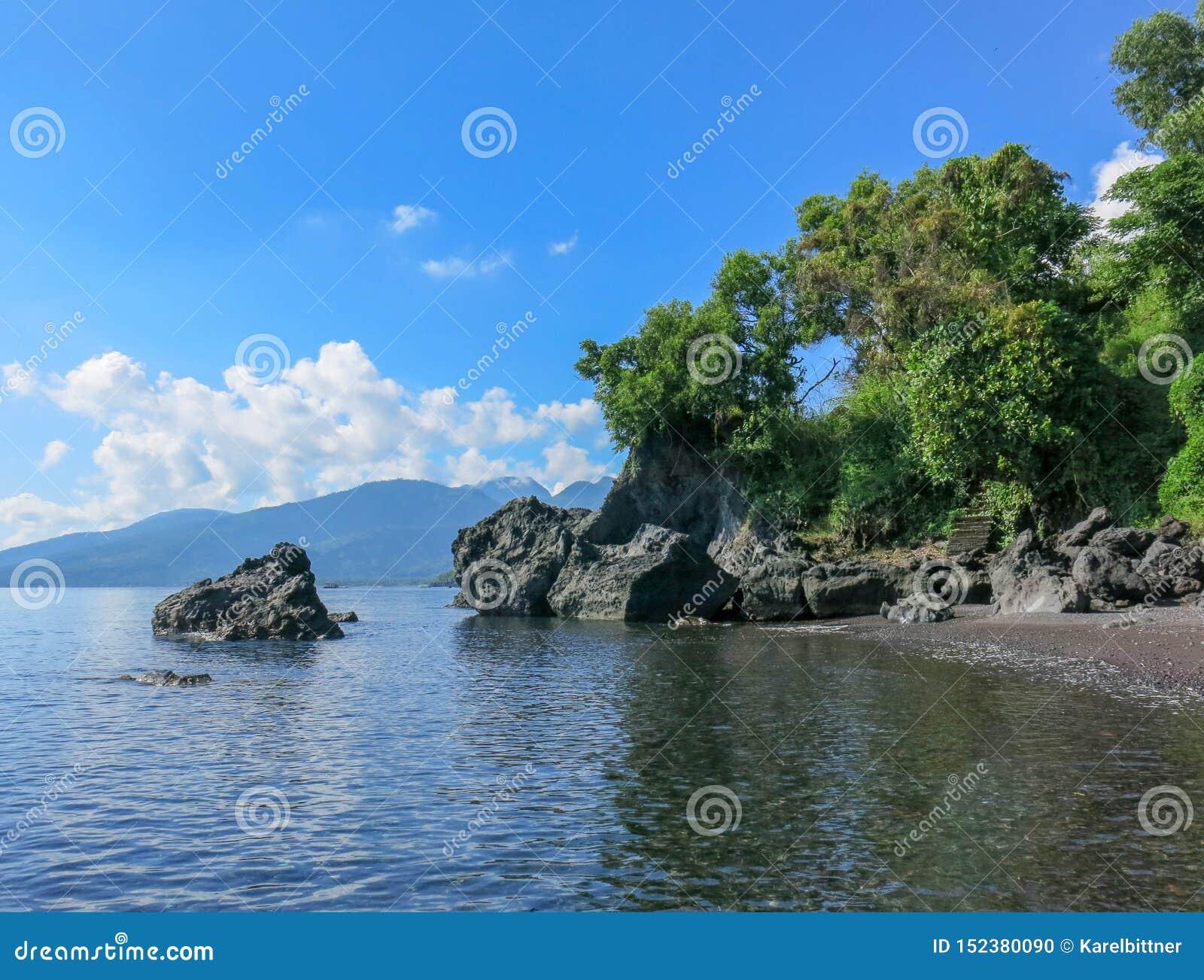 Romantisch maagdelijk strand met zwart zand Rotsvormingen van vulkanische oorsprong de klippen van abstracte vormen puilen boven
