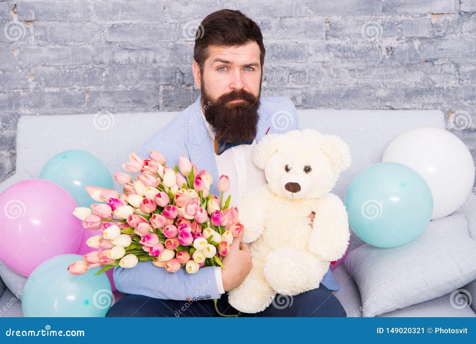 Καλλωπισμένος ατόμων καλά η ανθοδέσμη τουλιπών λουλουδιών λαβής δεσμών τόξων σμόκιν ένδυσης και μεγάλος teddy αντέχουν το παιχνίδ