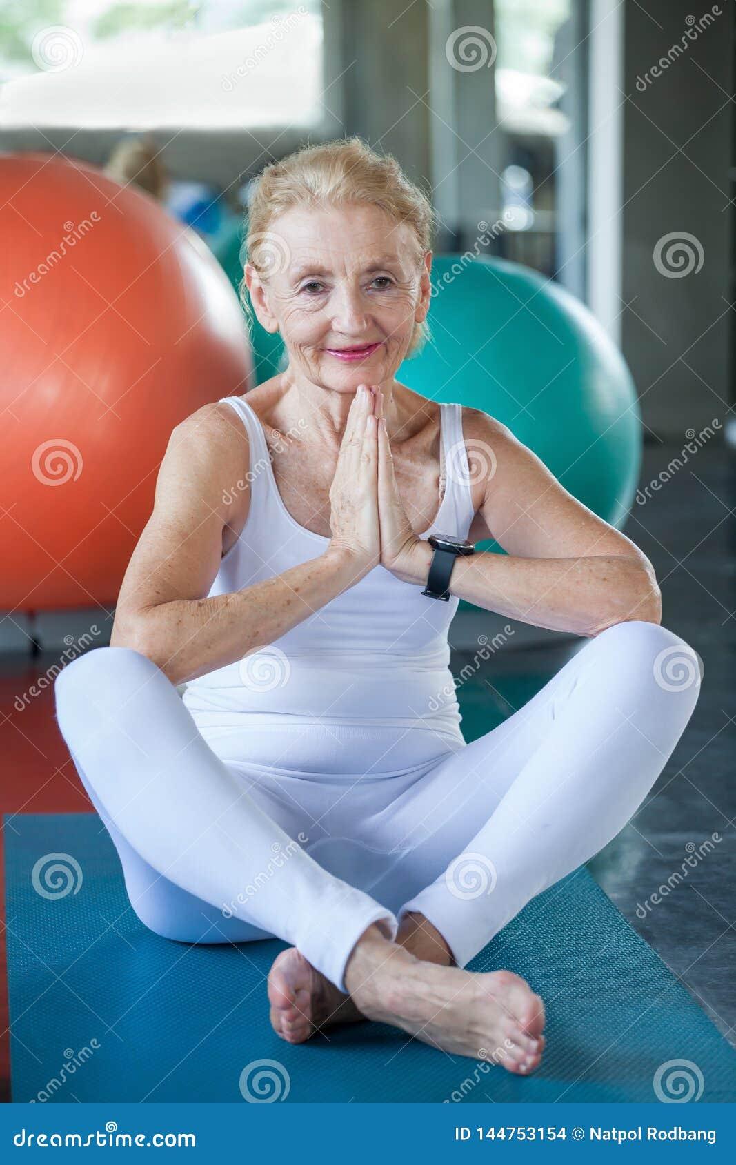 Старшая женщина делая йогу в спортзале фитнеса достигший возраста работать дамы Старая женская разминка Зрелая тренировка спорта