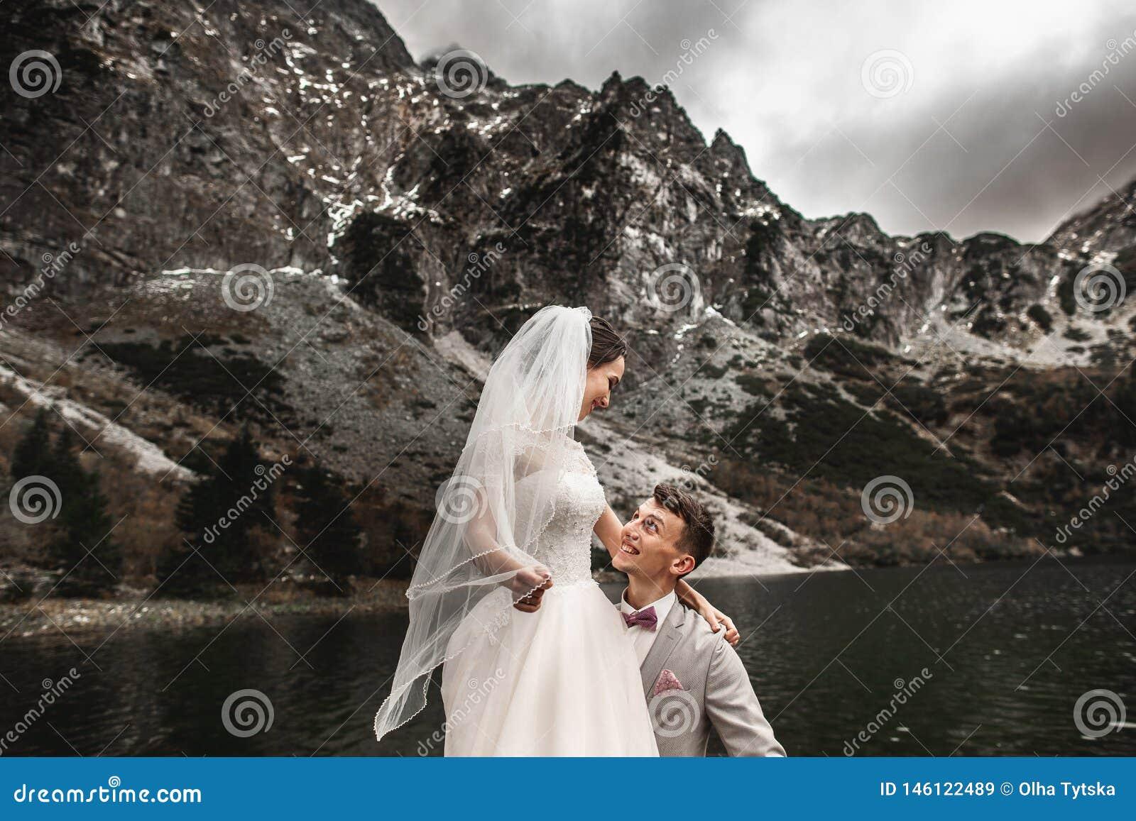 Hermosa sesión fotográfica de boda El novio rodea a su joven novia, a la orilla del lago Morskie Oko Polonia