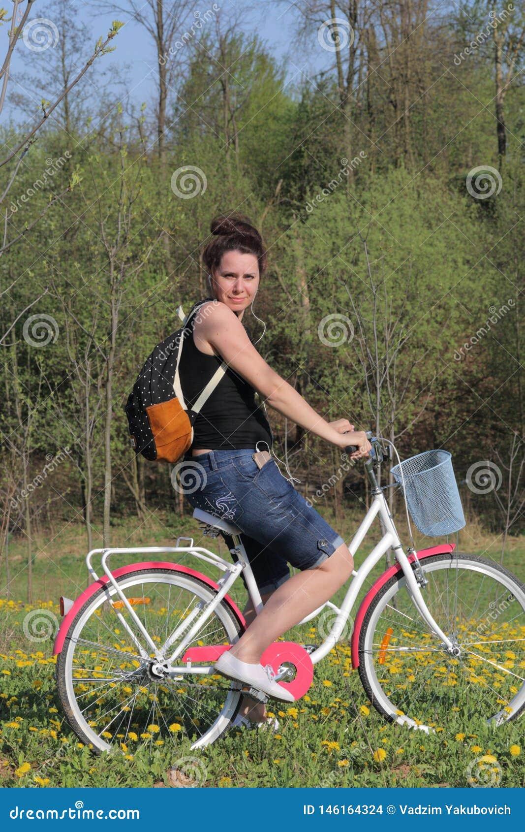 E Se sienta en una bicicleta, detrás de una mochila turística Los dientes de le?n est?n floreciendo, hierba joven son