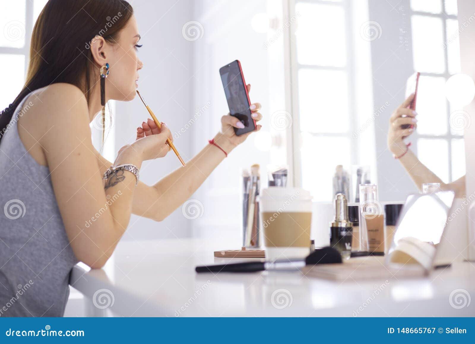 ?e?ska m?oda pi?kna dziewczyna z k?dzierzawym w?osy i makija?em pi?kna kobieta robi autoportretowi telefonem