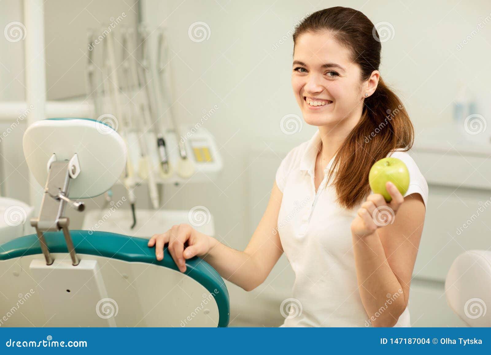?e?ski dentysta u?miecha si? i trzyma zielonego jab?ka, stomatologicznej opieki i zapobiegania poj?cia