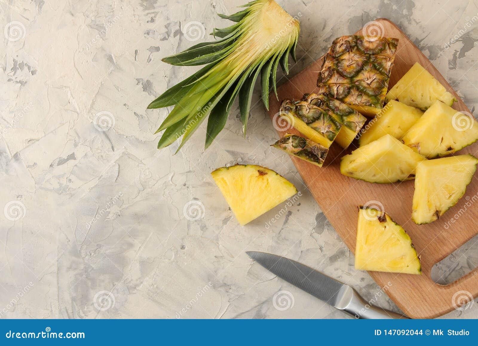 E Tranches d ananas sur une planche à découper sur un fond de ciment ?t? Vue sup?rieure