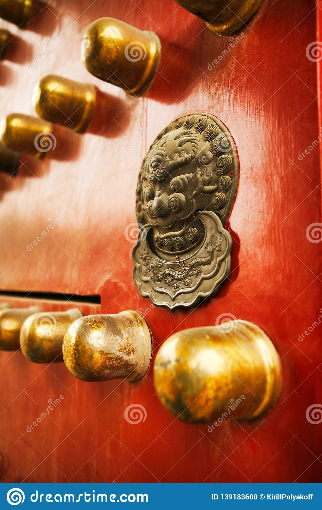 Richly decorated red wooden door with decoration in the Forbidden City, Beijing, China.