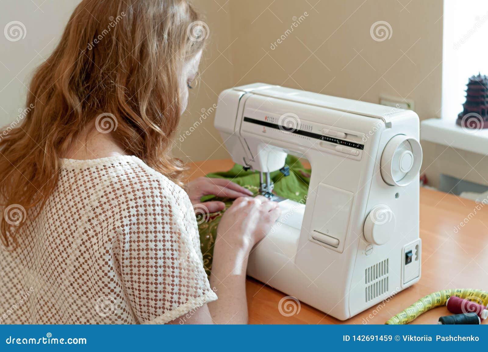 Eamstress che si siede alla macchina per cucire bianca e che lavora vicino alla finestra