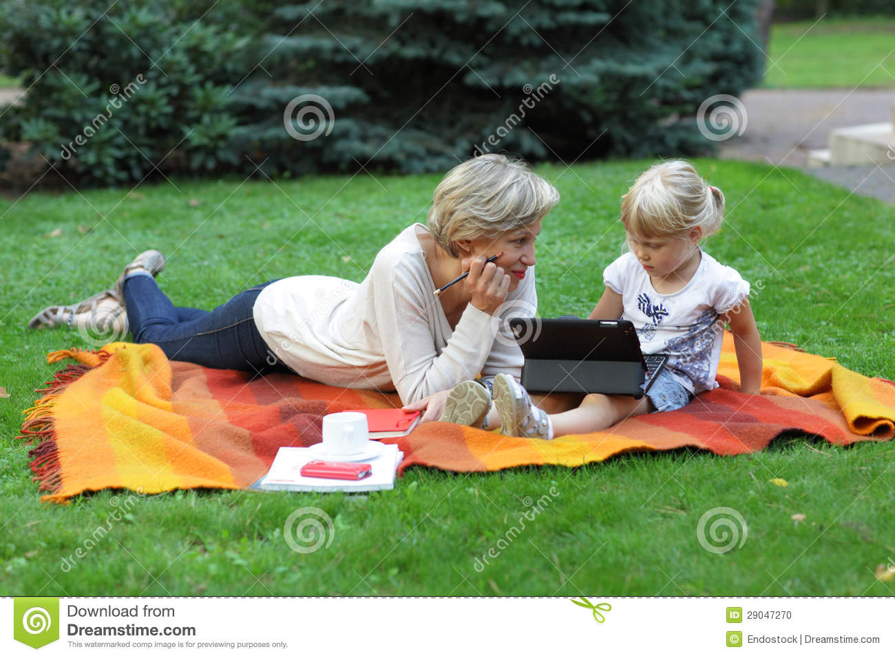 Early learning - mother watching her daughter using tablet