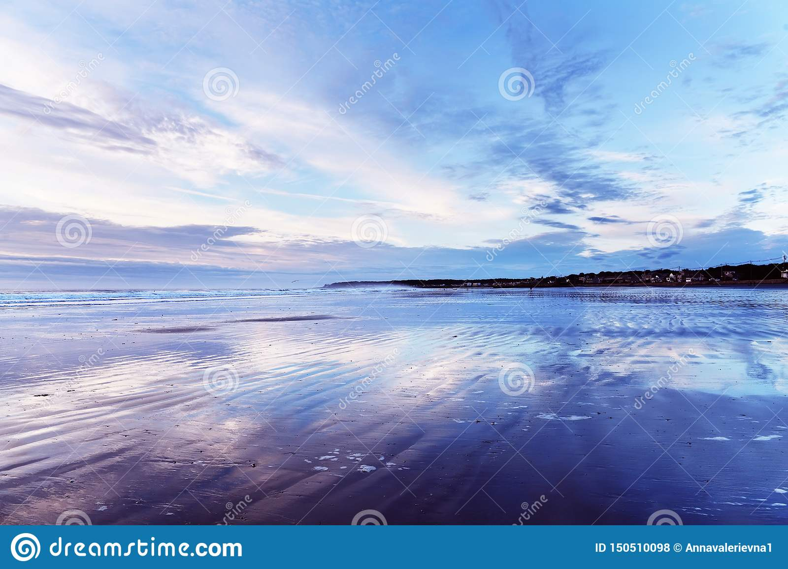 Early morning on the Atlantic coast. Reflection of the dawn sky in the water on the sand. USA. Maine.
