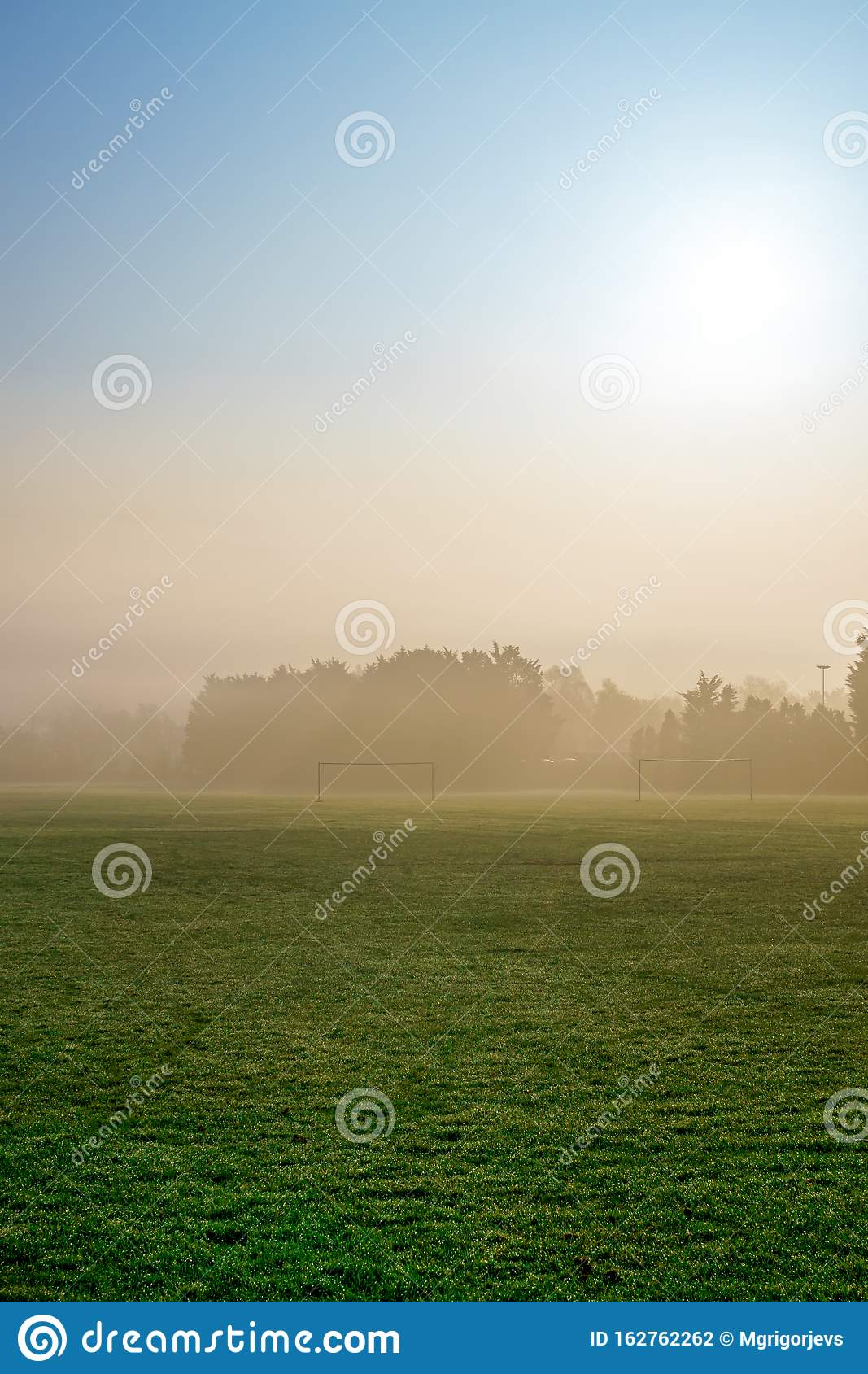 Early Morning Fog And Sunrise On Football Field With