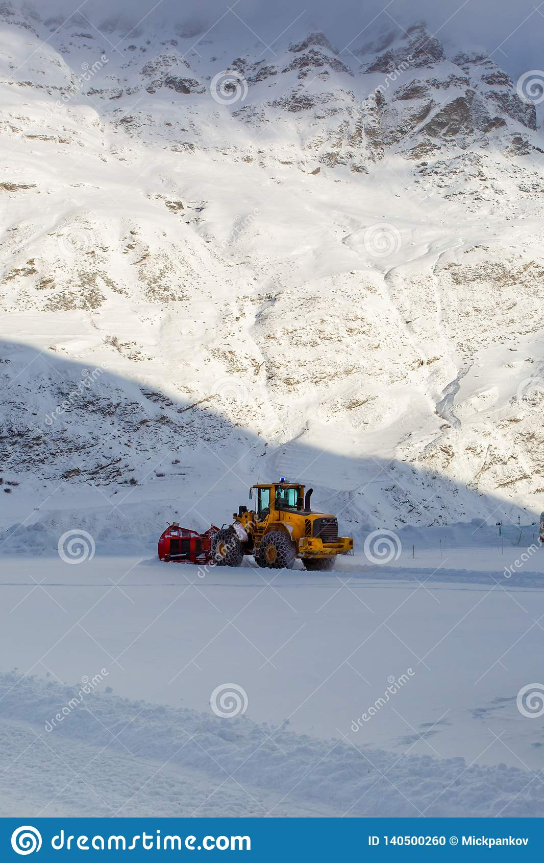 Early morning works equipment for snow removal in the mountains