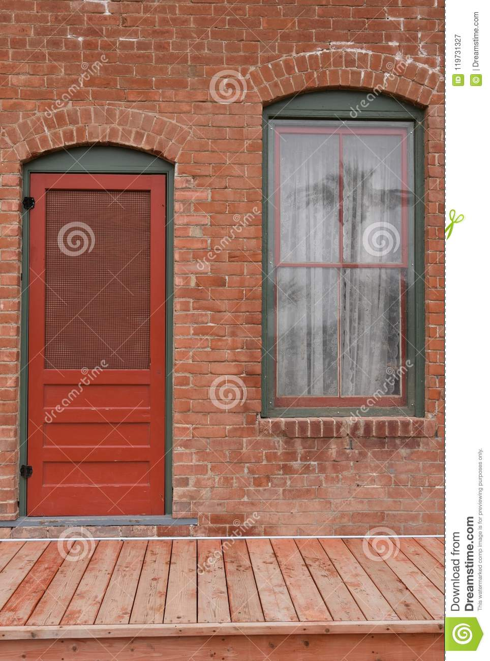 Window and red door on brick building with palm tree reflected in window