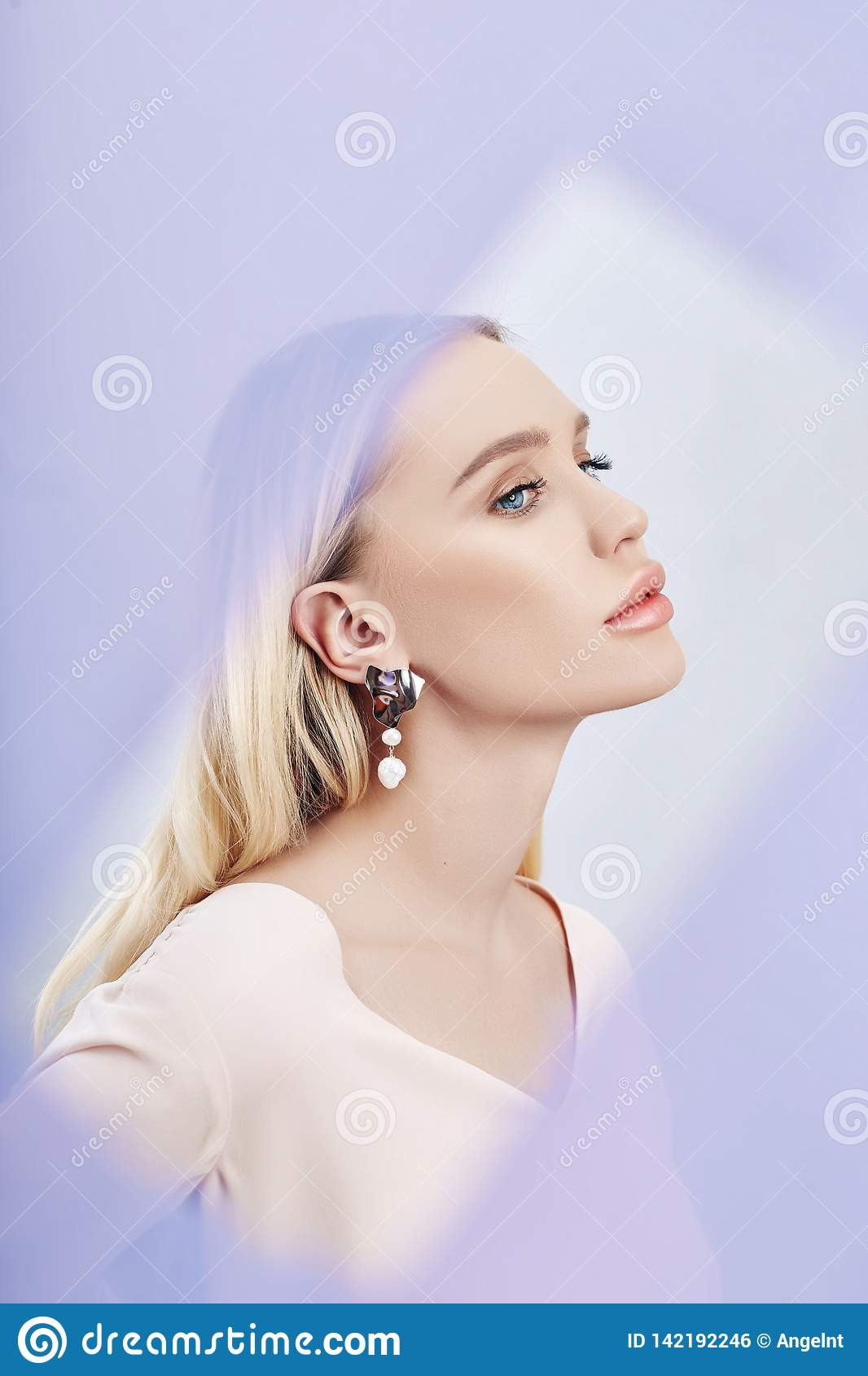 Earrings and jewelry in ear of a sexy blonde woman through a transparent colored fabric. Perfect blonde girl, gorgeous mysterious