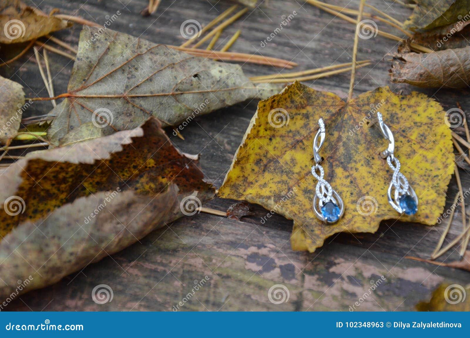 Earrings monili con topazio o zaffiro grande pietra blu su un fondo d annata Autunno Foglie