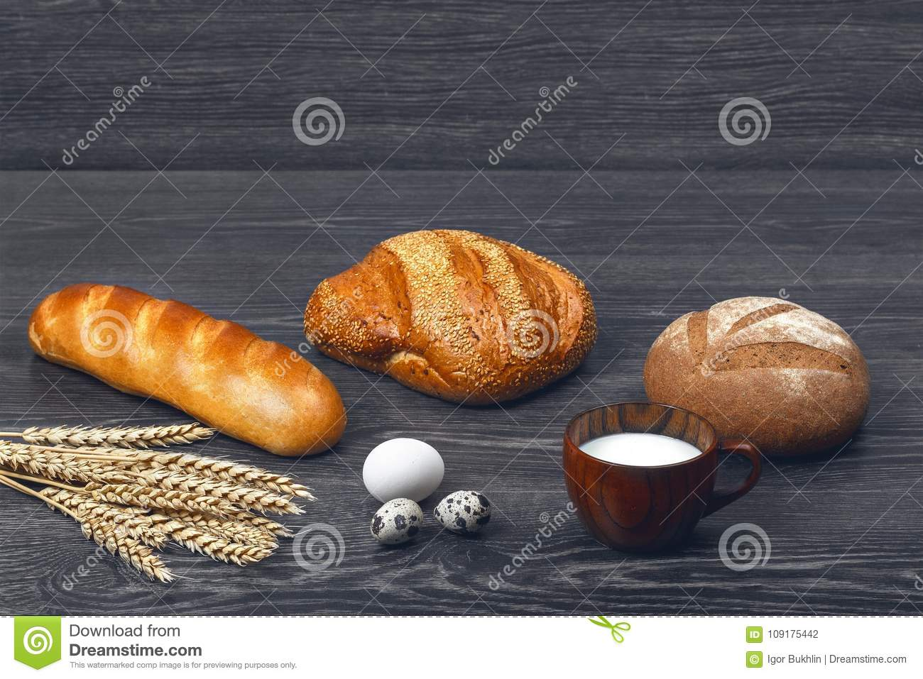 Ears of wheat, chicken and quail eggs, glass of milk, freshly baked bread and a loaf on wooden background.