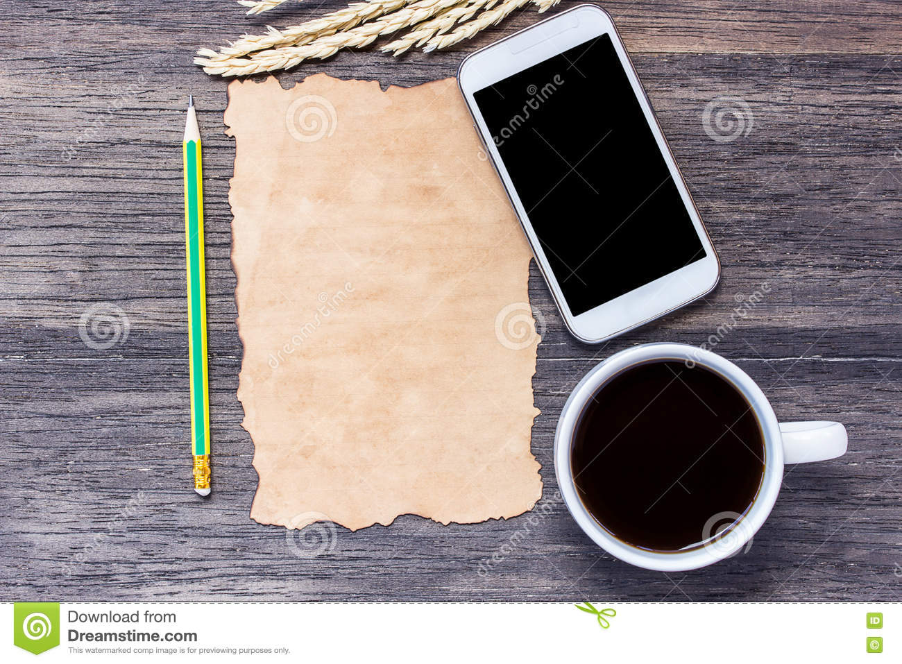 Ears of wheat,smart phone and old paper with cup of coffee