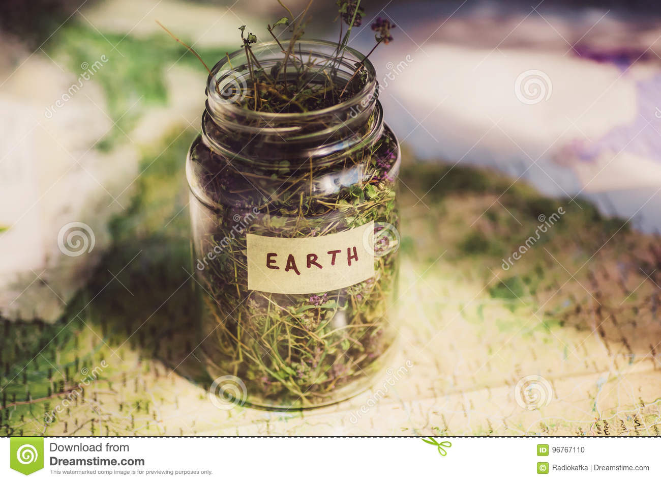 Earth on the geographic map and dry herb in a glass jar as a symbol royalty free stock photo gumiabroncs Gallery