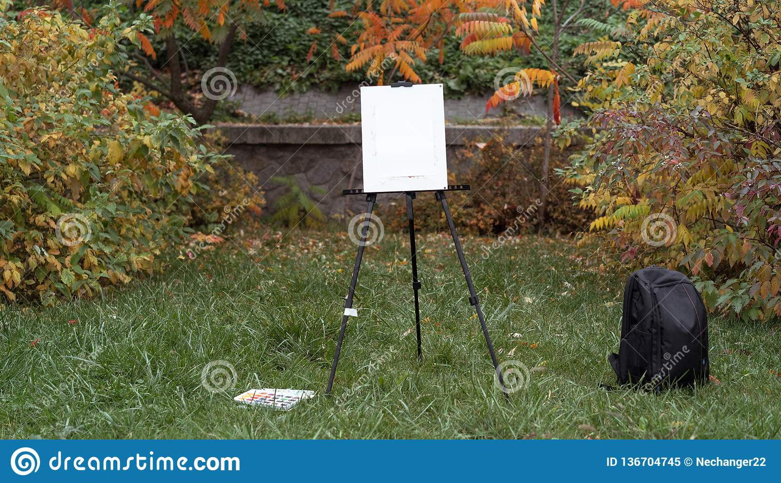 Easel, black backpack and paints are standing on the grass in the autumn park